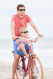 Family biking at the beach. Happy family of father and son enjoying their time together while biking at the beach Stock Photo