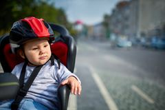 Family biking in the city. Little beautiful girl wearing helmets in bicycle seat. Royalty Free Stock Photo