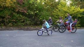 Family biking in park in bright sunshine