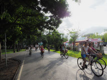 Family biking together in a park in a park in Bangkok. Stock Photo