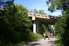 Family Biking Under Bridge. Family riding on a paved bikepath through woods under a highway bridge. Horizontal format Royalty Free Stock Image