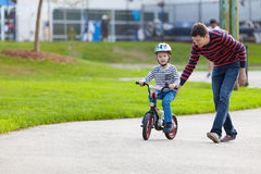 Family biking. Young father teaching his smiling son how to ride a bike Royalty Free Stock Photography