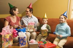 Family birthday party. Caucasian family wearing party hats and celebrating a birthday party royalty free stock photo