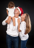 Family on a black background. Santa's hat with dad royalty free stock photo