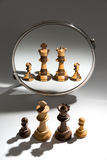 A family of black and white is looking in a mirror to see themselves as a black and white colored family. A family of two back and two white chess pieces is Stock Photos