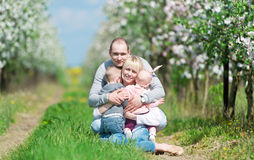 Family among the blossoming apple-trees. Stock Images