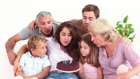 Family blowing candles on chocolate cake Royalty Free Stock Photos