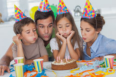 Family blowing candles together Royalty Free Stock Photography