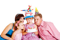 Family blowing out candles Stock Photo