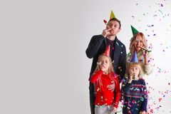 Family blowing party trumpets with confetti stock images