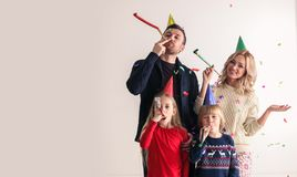 Family blowing party trumpets with confetti stock image