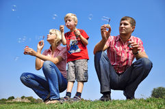 Family blowing soap bubbles Royalty Free Stock Images