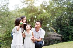 Family blowing soap bubbles. Asian family outdoors activity. Parents and children blowing soap bubbles at green park royalty free stock photo