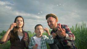 Family blowing soap bubbles and laughing in slow motion, little boy with mum and daddy in plaid shirts have fun during. Weekend at green meadow stock video footage