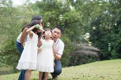 Family blowing soap bubbles at park. Asian family outdoors activity. Parents and children blowing soap bubbles at park stock image