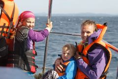 Family on a blue whale watching trip. Smiling girl in safety jacket on a boat trip. Mother holding baby royalty free stock photo
