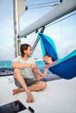 Family on board of sailing yacht. Family of father and cute girl relaxing in the hammock set on the sail boat while sailing in the open sea stock photo