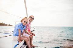 Family on board of sailing yacht. Father and daughter on board of sailing yacht having summer travel adventure stock images