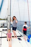 Family on board of sailing yacht. Mother and kids on board of sailing yacht having summer travel adventure royalty free stock images
