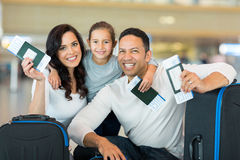 Family boarding pass. Happy family holding boarding pass and passport at airport Stock Photo