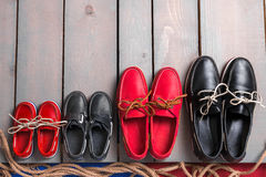 Family boat shoes on wooden background. Four pair of red and black boat shoes on grey desk with rope. Top view, copy Royalty Free Stock Images