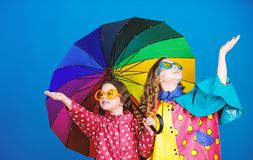 Family bonds. Small girls in raincoat. happy small girls with colorful umbrella. rain protection. Rainbow. autumn royalty free stock photo