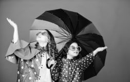 Family bonds. Small girls in raincoat. happy small girls with colorful umbrella. rain protection. Rainbow. autumn royalty free stock image