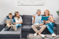 Family with book and laptop Stock Photos