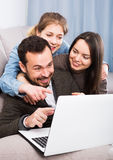 Family booking hotel online on laptop. Young family booking hotel online on laptop together at home Stock Photo