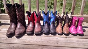 Family Boots. The cowboy boots of a family of five on a deck in the sunshine Stock Photography