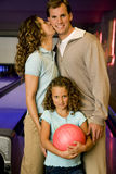 Family in a bowling alley, daughter holding a red bowling ball Royalty Free Stock Image