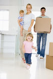 Family with box moving into new home smiling stock photo