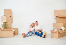 A family with boxes moves to a new house against a white wall. royalty free stock images