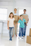 Family with boxes moving into new home smiling Stock Photo