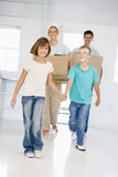 Family with boxes moving into new home smiling Stock Photos