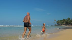 Family of boy and daddy runs in shallow water at beach