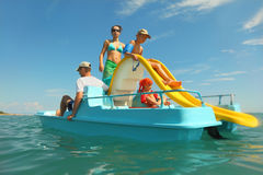 Family with boy and girl on pedal boat. Happy family with boy and girl on pedal boat with yellow slide in sea, view from water, shot from waterproof case Stock Photo