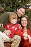 Family with boy sitting in front of Christmas tree Stock Images
