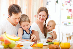 Family breakfast. Young happy family with two kids having breakfast together Royalty Free Stock Photos