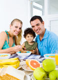 Family breakfast. Happy young family of two parents and toddler boy at breakfast table Stock Image