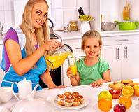 Family  breakfast with child at kitchen. Mom pours Stock Photo