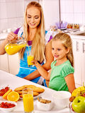 Family  breakfast with child at kitchen. Mom pours Royalty Free Stock Image