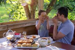Family Breakfast in a country house. Father and son pretending faces with pancakes royalty free stock photography