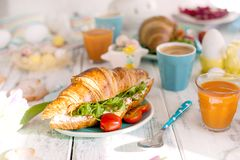 A family breakfast of croissants with rocket salad and cheese and aromatic coffee. Fresh tulips of pink color and eggs of royalty free stock images