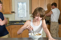 Family breakfast fun - teen brothers having cereal: candid shots Royalty Free Stock Images