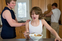 Family breakfast fun - teen brothers having cereal: candid shots Royalty Free Stock Photo