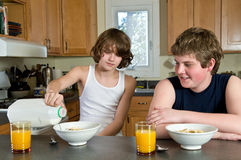 Family breakfast fun - teen brothers having cereal: candid shots Royalty Free Stock Image