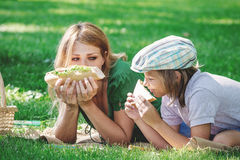Family breakfast on grass. Mom and son eating sandwich Royalty Free Stock Photo