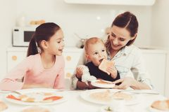 Family Breakfast. Mom Is Feeding A Little Son. Family Eating. Mom Is Feeding A Little Son At The Kitchen. Family Relationship Concept. Having Fun During The royalty free stock image