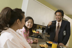 Family At Breakfast Table With Father Ready For Work Stock Images